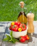 Frische reife Tomaten, Olivenölflasche, Pfefferschüttel-apparat und Kräuter Stockbild