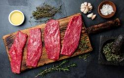 Frische Rindfleischsteaks des rohen Fleisches Rindsfilet auf hölzernem Brett, Gewürze, Kräuter, Öl auf Schiefergrauhintergrund Le Stockfoto