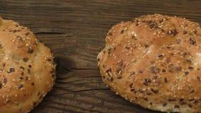 Frische Roggenbrötchen mit Samen des indischen Sesams auf einem hölzernen Hintergrund stock footage