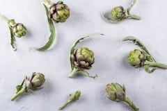 Frische rohe Artischocken auf grauem Hintergrund Reife organische Artischocke Lizenzfreie Stockfotos