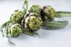 Frische rohe Artischocken auf grauem Hintergrund Reife organische Artischockenblume Lizenzfreie Stockbilder