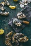 Frische rohe Austern und Zitrone auf Eis Würfeln auf Holztisch lizenzfreie stockfotos