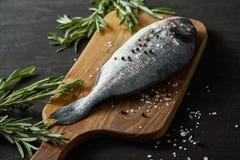 Frische rohe dorada Fische mit Rosmarin, Pfeffer und Salz auf einem hölzernen Brett und einer schwarzen Tabelle lizenzfreie stockfotografie