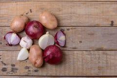 Frische rohe Kartoffeln und Zwiebel auf hölzernem Hintergrund Lizenzfreies Stockbild