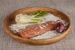 Frische rohe Lachse auf einem hölzernen Behälter mit Petersilie, Salz und Sellerie Stockfotos