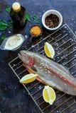 Frische rohe Lachse vorbereitet, am dunklen Hintergrund zu kochen lizenzfreie stockbilder