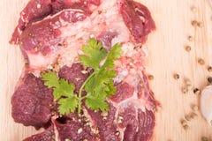 Frische rohe Rindfleischfleischscheiben und Knoblauch, Pfeffer auf hölzernem Lizenzfreies Stockfoto