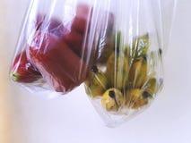 Frische Rose Apples und reife Bananen in den transparenten Plastiktaschen Lizenzfreie Stockfotografie