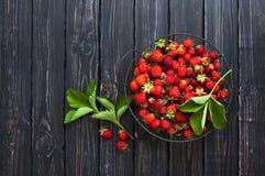 Frische rote Erdbeere in einer Schüssel auf einem dunklen rustikalen hölzernen Hintergrund, Draufsicht mit Kopienraum Lizenzfreies Stockbild