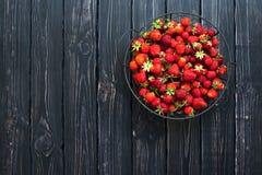 Frische rote Erdbeere in einer Schüssel auf einem dunklen rustikalen hölzernen Hintergrund, Draufsicht mit Kopienraum Lizenzfreies Stockfoto