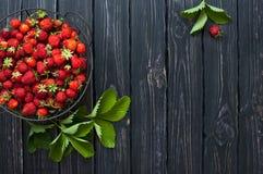 Frische rote Erdbeere in einer Schüssel auf einem dunklen rustikalen hölzernen Hintergrund, Draufsicht mit Kopienraum Lizenzfreie Stockfotos