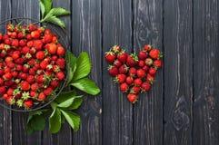 Frische rote Erdbeere in einer Schüssel auf einem dunklen rustikalen hölzernen Hintergrund, Draufsicht mit Kopienraum Stockbild