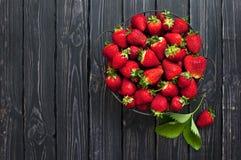 Frische rote Erdbeere in einer Schüssel auf einem dunklen rustikalen hölzernen Hintergrund, Draufsicht mit Kopienraum Stockbilder