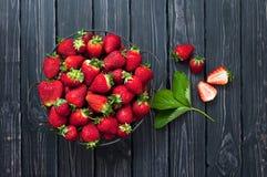 Frische rote Erdbeere in einer Schüssel auf einem dunklen rustikalen hölzernen Hintergrund, Draufsicht mit Kopienraum Lizenzfreie Stockfotografie