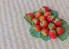 Frische rote Erdbeere und Blatt vom Bauernhof auf gesponnener Oberfläche Stockfoto