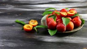 Frische rote Pflaumen mit Blättern auf einer keramischen Platte Auf einem dunklen Hintergrund Freier Platz für Text Flache Lage lizenzfreie stockfotografie
