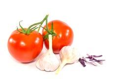 Frische rote Tomate und Knoblauch auf weißem Hintergrund Stockfoto