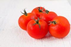 Frische rote Tomaten auf weißem Holztisch Lizenzfreies Stockfoto