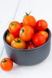 Frische rote Tomaten in der schwarzen Schüssel auf weißem Holztisch Stockbild