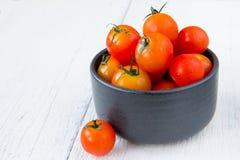 Frische rote Tomaten in der schwarzen Schüssel auf weißem Holztisch Stockfotografie
