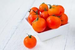 Frische rote Tomaten in der weißen Schüssel auf weißem Holztisch Stockbild