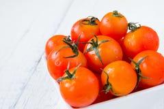 Frische rote Tomaten in der weißen Schüssel auf weißem Holztisch Stockfoto