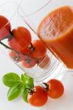 Frische rote Tomaten mit Basilikumblatt und -saft Lizenzfreies Stockbild