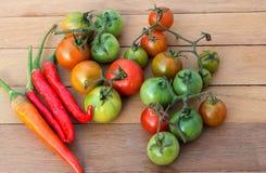 Frische rote Tomaten und Pfeffer gesetzt auf einen Holztisch Lizenzfreies Stockbild