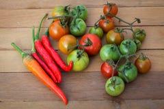 Frische rote Tomaten und Pfeffer gesetzt auf einen Holztisch Lizenzfreies Stockfoto