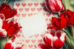 Frische rote Tulpen und leere Grußkarte mit Herzen, Draufsicht, Rahmen Stockfotos