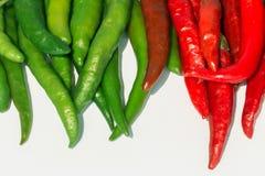 Frische rote und grüne Paprikas auf weißem Hintergrund Lizenzfreie Stockfotos