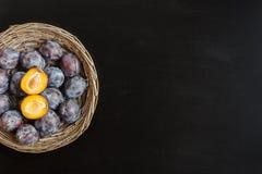 Frische süße Pflaume im runden rustikalen Weidenkorb auf schwarzem chalkboa Stockbild