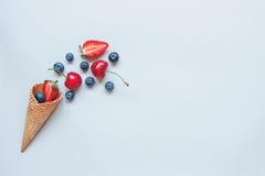 Frische saftige Beeren und süßer Waffelkegel auf dem blauen Hintergrund, Draufsicht Lizenzfreie Stockbilder