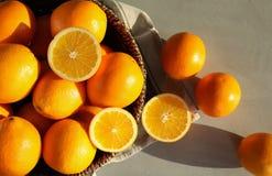 Frische saftige Orangen im Weidenkorb auf Tabelle stockfotografie