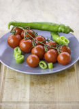 Frische saftige rote Kirschtomaten geschnitten von der grünen Peperoni Lizenzfreie Stockfotografie