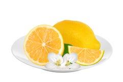 Frische saftige Zitrone mit grünem Blatt und Blumen auf der Platte lokalisiert Stockbilder