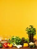 Frische Salatbestandteile und gelber Hintergrund Stockfotografie
