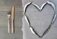Frische Sardine in der Herzform und -tischbesteck Stockfoto