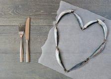 Frische Sardine in der Herzform und -tischbesteck Lizenzfreies Stockfoto