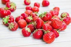 Frische schöne Erdbeeren liegt auf einem weißen Holztisch stockbilder