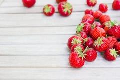Frische schöne Erdbeeren liegt auf einem weißen Holztisch stockbild