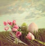 Frische Schnitttulpen mit Eiern im hohen Gras Lizenzfreies Stockfoto