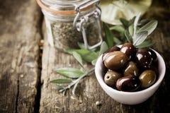 Frische schwarze Oliven und Kräuter Stockbilder