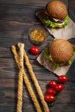 Frische selbst gemachte Burger und Breadsticks auf hölzernem Hintergrund Stockbild