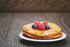 Frische selbst gemachte Pfannkuchen mit Beeren und Ahornsirup Lizenzfreie Stockbilder