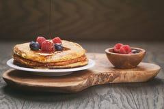 Frische selbst gemachte Pfannkuchen mit Beeren und Ahornsirup Stockfoto