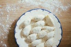 Frische selbst gemachte Ravioli, Mehlklöße oder pelmeni bedeckt im Mehl auf einem Holztisch Roh, ungekocht Lizenzfreie Stockfotografie