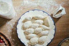 Frische selbst gemachte Ravioli, Mehlklöße oder pelmeni bedeckt im Mehl auf einem Holztisch Roh, ungekocht Stockbild