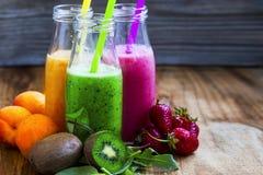 Frische Smoothies in den Flaschen in drei Farben: Grün mit Spinat a Lizenzfreie Stockfotografie