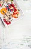 Frische Sommerbeeren mit muesli auf weißem Küchenbehälter auf schäbigem schickem hölzernem Hintergrund, Draufsicht, Platz für Tex Lizenzfreies Stockbild